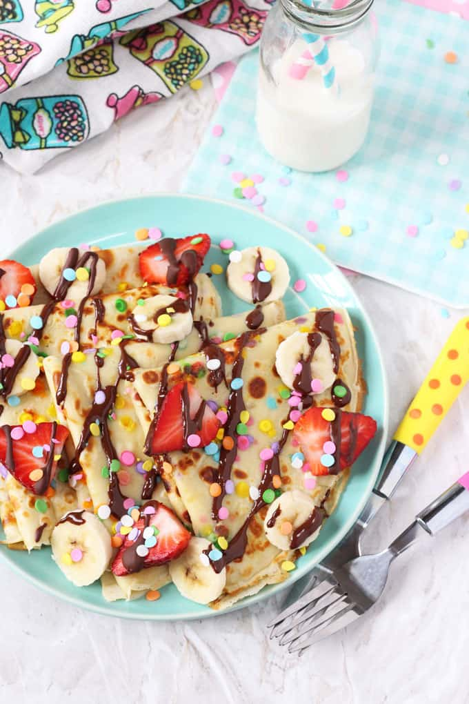 Pancakes made super fun for kids with confetti sprinkles and topped with bananas, strawberries and chocolate!