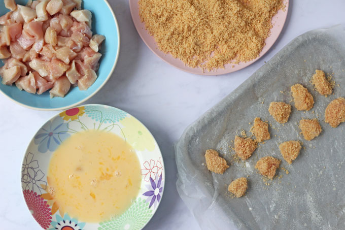 Making Popcorn Chicken with chicken pieces, egg mixture and a Rice Krispie coating