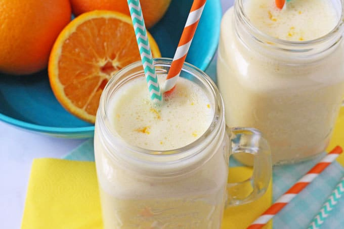 Close up of Orange Smoothie with orange and green straws