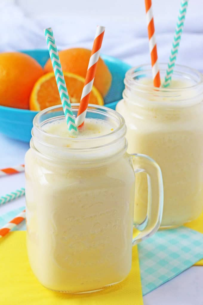 Creamy Orange Smoothie with orange and blue straws and whole oranges in the background