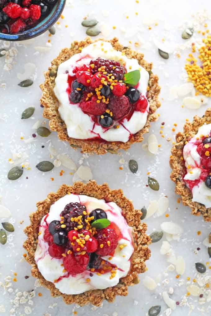 the finished breakfast tarts topped with fresh berries, nuts and seeds