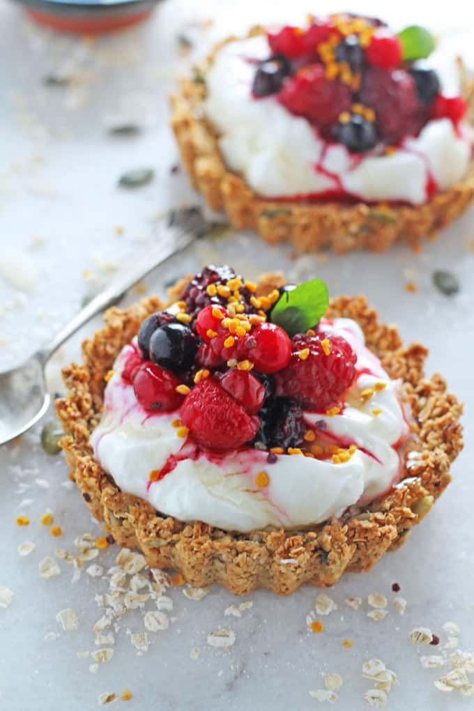 2 Granola Crust Breakfast Tarts filled with yogurt and berries on a marble background with a spoon