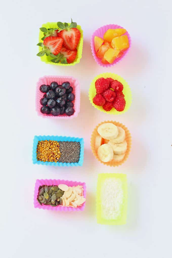 a selection of multi coloured silicone muffins cases filled with various nuts, seeds and berries