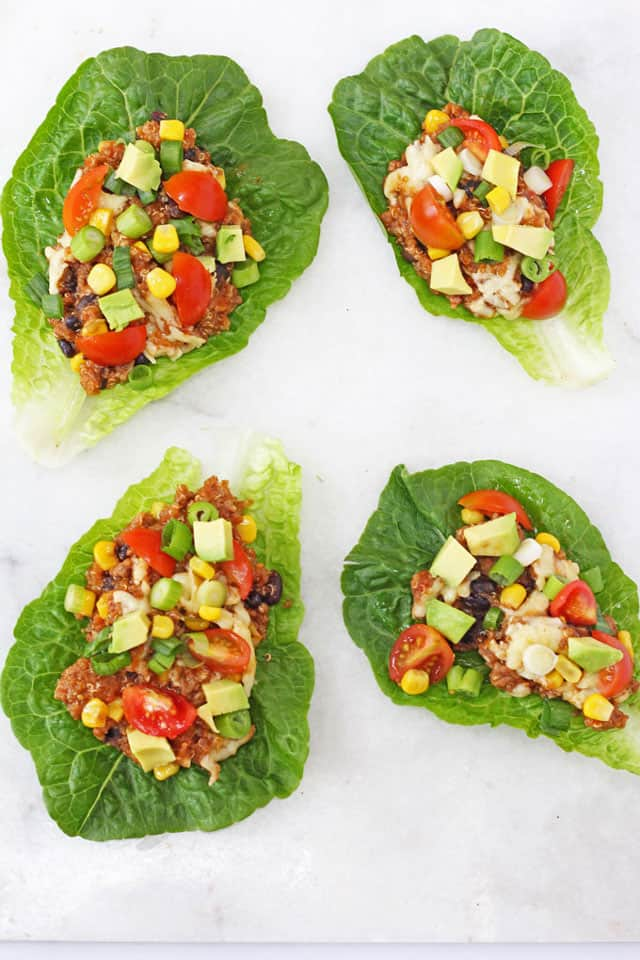 4 Slow Cooker Quinoa Lettuce Cups on a white marble background