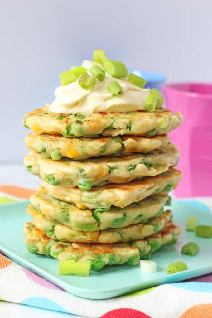 A stack of Pea & Sweetcorn Fritters on a green plate and topped with creme fraiche and spring onions