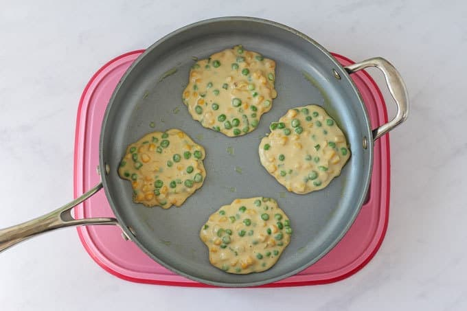 Pea & Sweetcorn Fritters in a frying pan