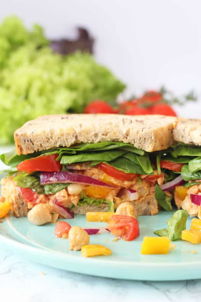 A delicious vegan sandwich packed with spicy sriracha chickpeas, lettuce, spinach, tomatoes and peppers. Perfect for a 2 minute healthy lunch for busy parents!