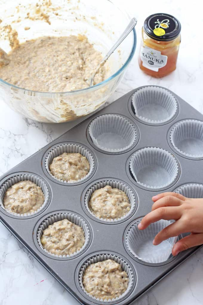 putting muffin mixture into muffin cases