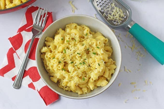 A big bowl of hidden vegetable macaroni cheese with grated cheese and a cheese grater