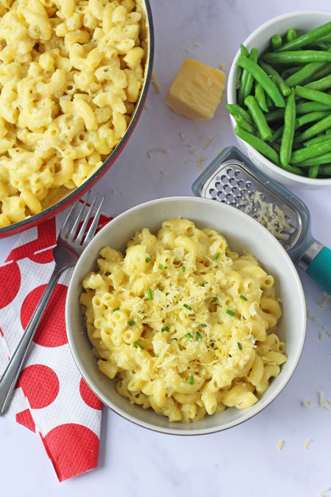 A bowl of Mac & Cheese with a side of green beans