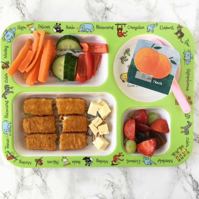 Green kids plate with fish fingers, cheese and other items for dinner