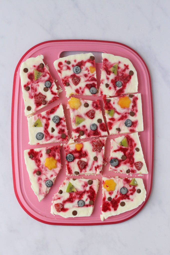 Frozen Yogurt Bark cut up on a pink board