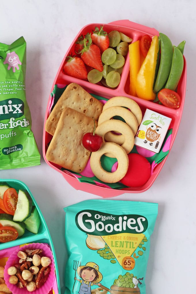 Pink lunch box filled with fruit, vegetables and crackers