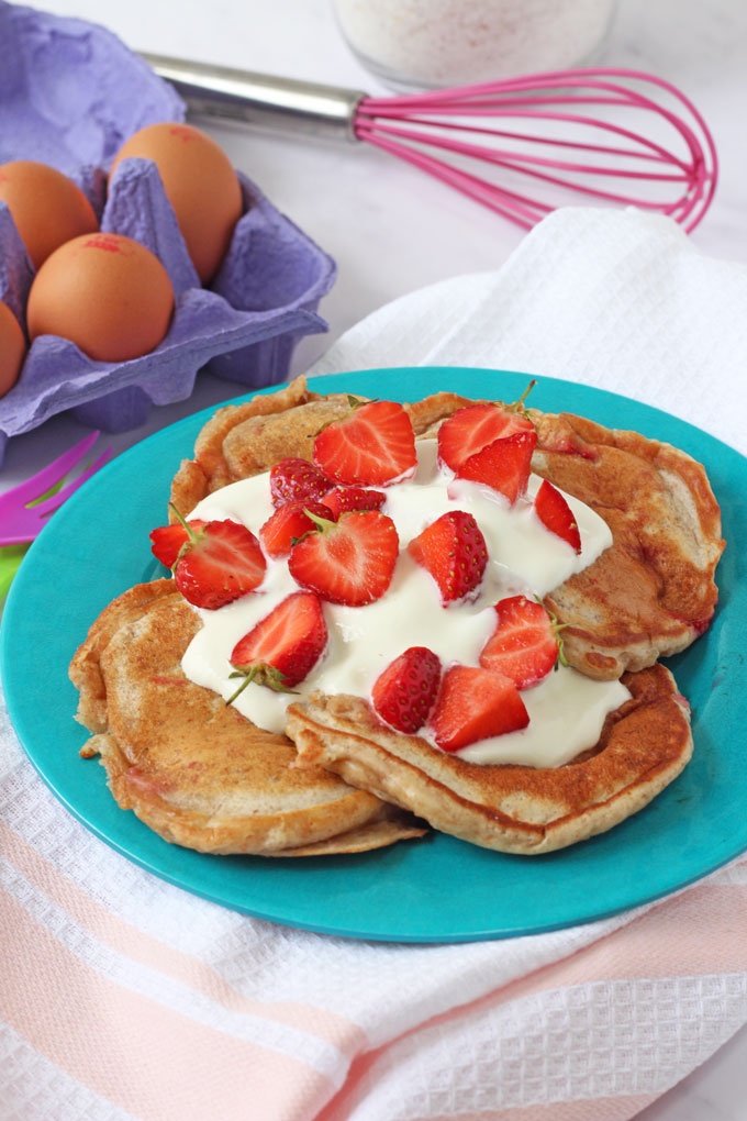Pancakes topped with yogurt and strawberries on a blue plate