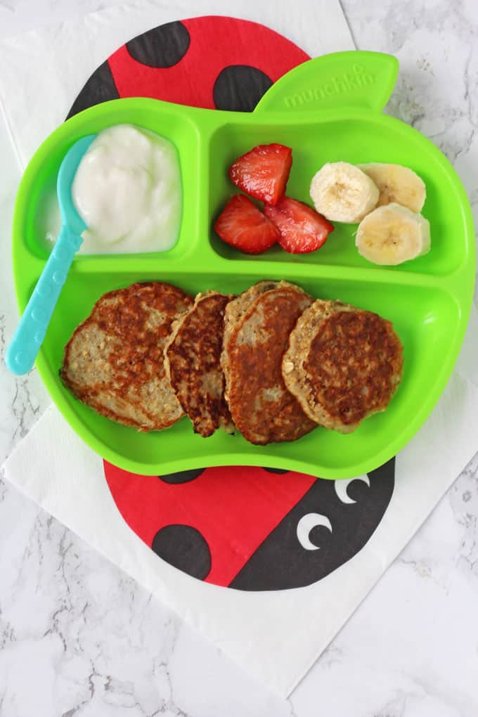 Banana & Oat Pancakes served on a divided plate with fruit and yogurt
