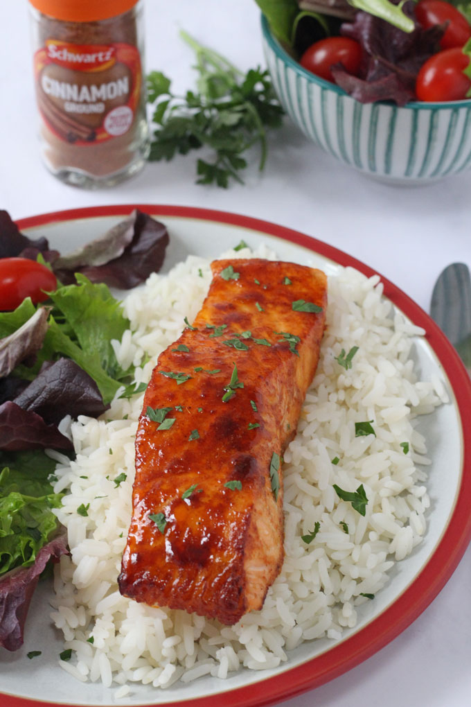 Cinnamon Spiced Salmon served with rice and a side salad.