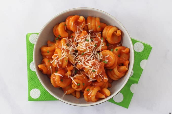 Pasta with red lentil sauce and topped with grated cheese