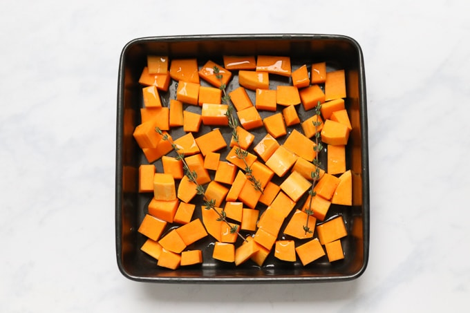 butternut squash in a roasting tin with olive oil and fresh thyme