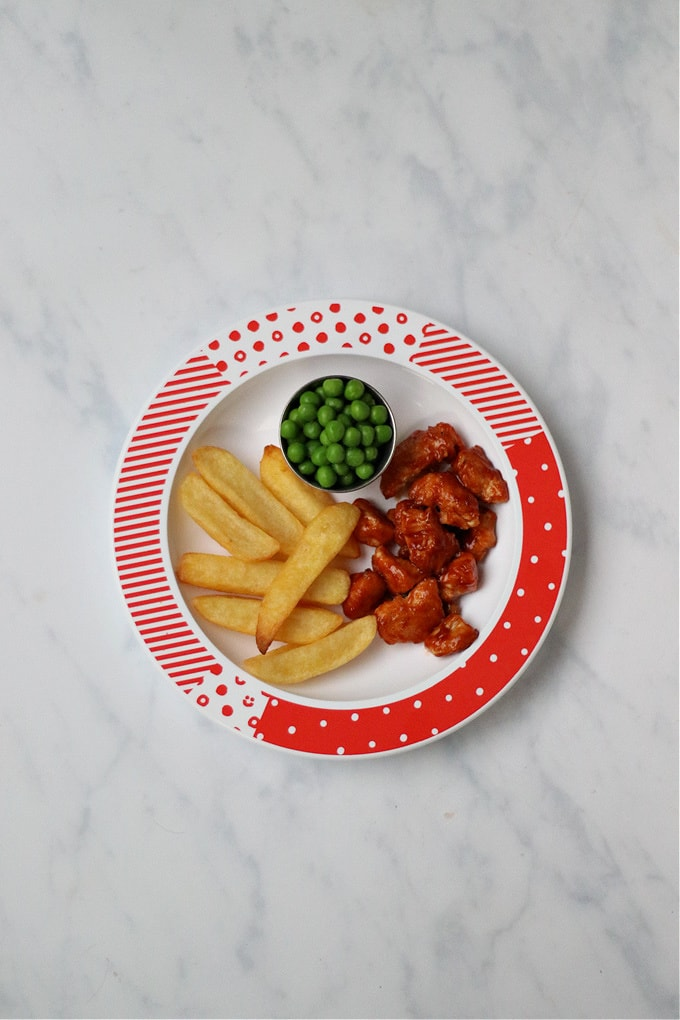 Buffalo chicken served for kids with chips and peas