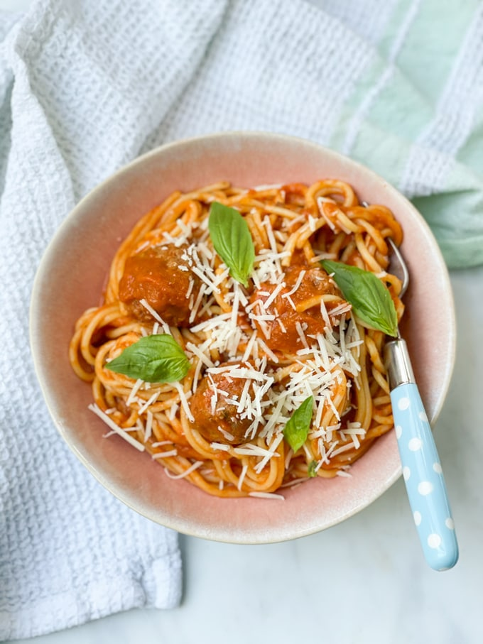 Slow cooker spaghetti meatballs in a bowl served with parmesan and basil leaves