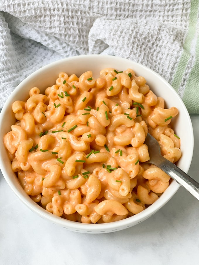 Buffalo Mac & Cheese served in a white bowl, topped with chopped chives