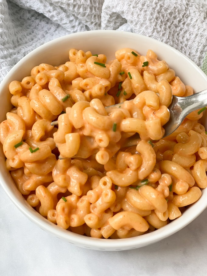 close up of buffalo mac & cheese on a fork in a white bowl