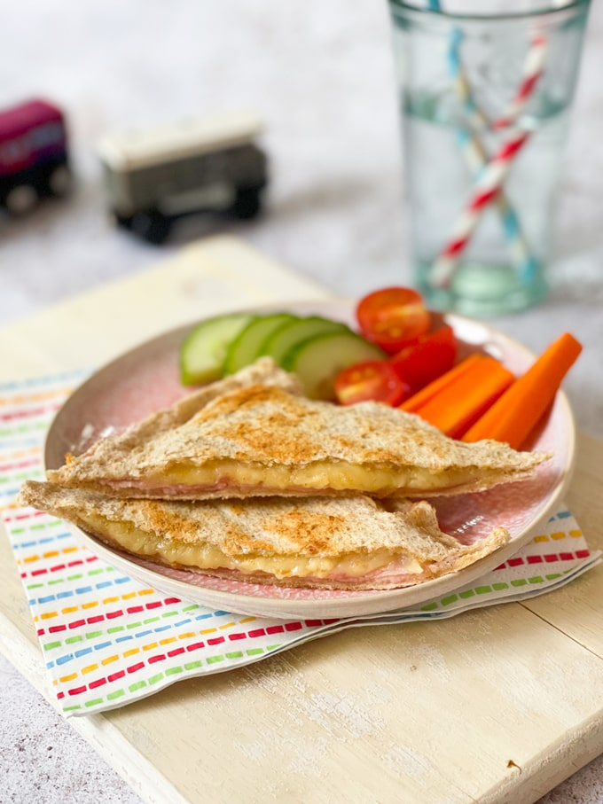 Cheese & Ham Toaster Toastie on a plate with cucumber, tomatoes and carrot batons