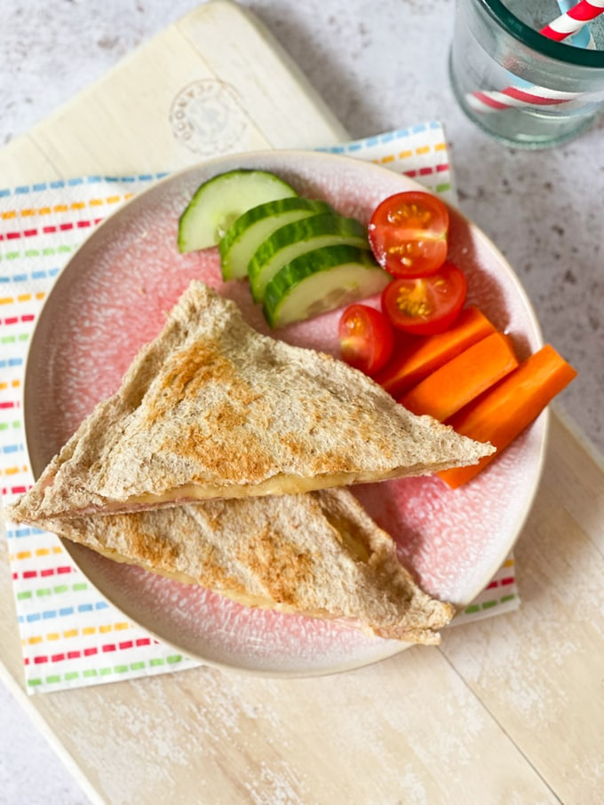 the finished toaster toastie served on a pink plate with crudites